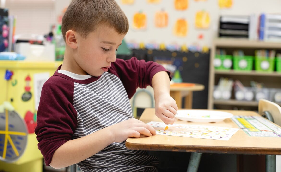 Young boy at school sitting in his desk working on school work
